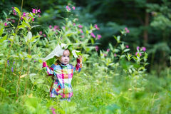Funny baby girl playing peek a boo in a park under huge leaves Stock Image