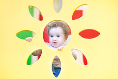 Funny baby girl playing peek-a-boo on playground Stock Image