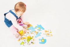 Funny baby girl playing with puzzle game for development Royalty Free Stock Image