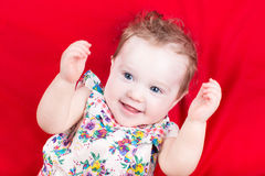 Funny baby girl playing on a red blanket Royalty Free Stock Photos
