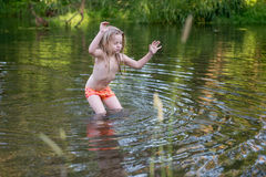 Funny baby girl playing in river Stock Photos