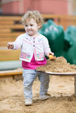Funny baby girl playing with sand on a playground Stock Images
