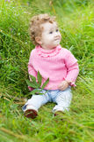 Funny baby girl playing with a snail in the garden Royalty Free Stock Image