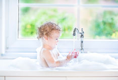 Funny baby girl playing with water and foam Royalty Free Stock Photography