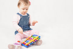 Funny baby girl playing by xylophone Stock Photo