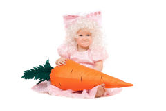 Funny baby girl plays with a carrot Stock Images