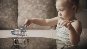 Funny baby girl plays with toy shopping cart royalty free stock images