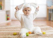 Smiling baby girl in rabbit costume sitying on rug in nursery royalty free stock images