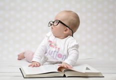 Funny baby girl reading a book. Funny portrait of a cute baby girl in glasses lying over a big book Royalty Free Stock Photography