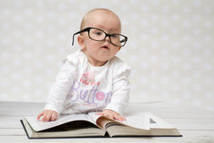 Funny baby girl reading a book. Funny portrait of a cute baby girl in glasses lying over a big book Stock Photo