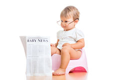 Funny baby girl reading newspaper on chamberpot Stock Photos