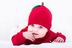 Funny baby girl in a red apple hat Royalty Free Stock Image