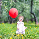 Funny baby girl with a red balloon in a garden. Funny baby girl playing with a red balloon in a garden Stock Photography