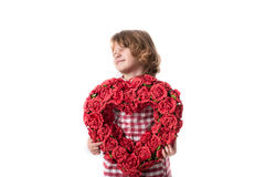 Funny baby girl in red checkered dress with  heart of red flower. Funny child girl in red checkered dress with a heart of red flowers, and the concept of Royalty Free Stock Photo