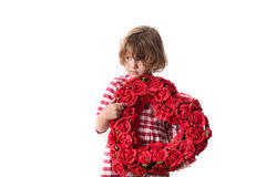 Funny baby girl in red checkered dress with  heart of red flower. Funny child girl in red checkered dress with a heart of red flowers, and the concept of Royalty Free Stock Image