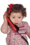 Funny baby girl with red telephone Stock Photography