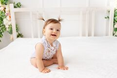 Funny baby girl six months old sitting in a bright beautiful room on a white bed in a lace bodysuit looking at the camera and