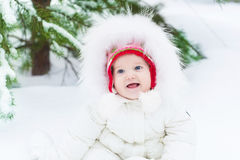 Funny baby girl in snow under Christmas tree Stock Images