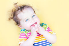 Funny baby girl sucking on her finger. Funny little baby girl sucking on her finger Royalty Free Stock Photography
