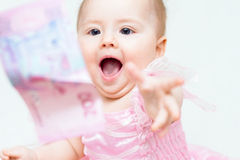 Funny baby girl try to catch banknote Stock Photography