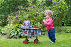 Funny baby girl with vintage doll stroller in garden Stock Photo