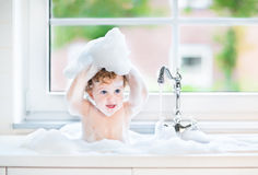 Funny baby girl in water and foam in big kitchen sink Stock Photography