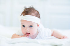 Funny baby girl with a white bow. Funny little baby girl with a white bow Royalty Free Stock Images