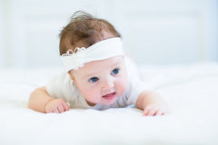 Funny baby girl with a white bow Stock Photo