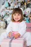 Funny baby girl in white and pink fleece pajamas sitting near Christmas tree and unpacking New Year gift.  Stock Photo