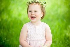 Funny baby girl in wreath of lilies smiling Stock Image