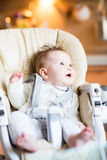 Funny baby in a high chair Royalty Free Stock Image