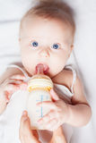 Funny baby holding a bottle with mothers breast milk Stock Images