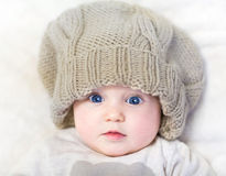 Funny baby in a huge knitted hat Stock Photos