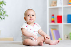 Funny baby kid girl sitting on floor in children room Stock Photography