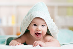 Funny baby kid under a hooded towel after bath Royalty Free Stock Image