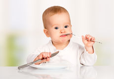 Funny baby with a knife and fork eating food Stock Images