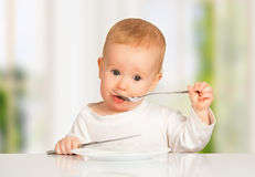 Funny baby with a knife and fork eating food Royalty Free Stock Photography