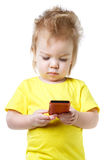 Funny baby looks at the screen of the smartphone Stock Images