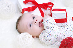 Funny baby lying with gift in hands Royalty Free Stock Image