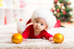 Funny baby lying on tummy wearing Santa hat and suit in front of Christmas tree Stock Photo