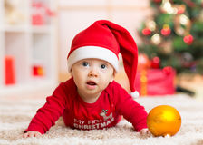 Funny baby lying on tummy wearing Santa hat and suit in front of Christmas tree Royalty Free Stock Photo