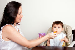 Funny baby messy eater. Beautiful happy mother or nanny feeds funny baby boy girl orange puree with spoon, infant eats messy, while sitting at table royalty free stock image