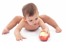 Funny baby playing with an apple. Royalty Free Stock Images