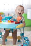 Funny baby playing in baby walker. Funny baby boy playing in baby walker at home Stock Photos