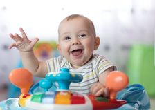 Funny baby playing in baby walker. Funny baby boy playing in baby walker at home Stock Photography