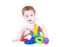 Funny baby playing with a colorful plastic pyramid Stock Photos