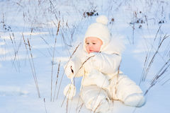 Funny baby playing with grass in a snow field Stock Images