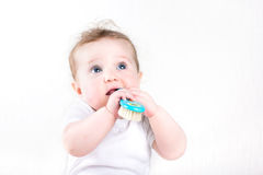 Funny baby playing with a hair brush Stock Photography