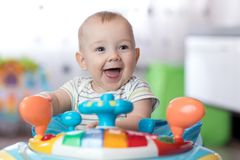 Funny baby playing in baby jumper Royalty Free Stock Image