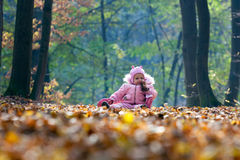 Funny baby playing with leaves Stock Photos